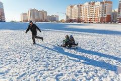 父亲和两个儿子sledding 库存图片