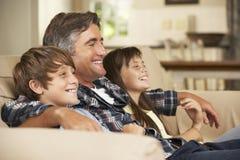 父亲和两个孩子在家坐一起看电视的沙发 库存照片