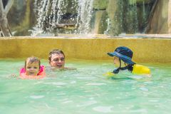 父亲和两个男孩在水池游泳 蓝色游泳热带假期的概念系列愉快的使用的池手段海运夏天浇灌 免版税库存照片