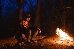 父亲和他的小儿子一起坐在晚上注册火的前面 远足在森林里 免版税图库摄影