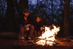父亲和他的小儿子坐注册在火前面的森林和在的烤蛋白软糖 免版税库存图片