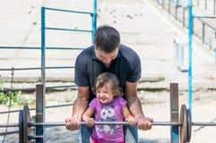 父亲和使用在公园的女婴 库存图片