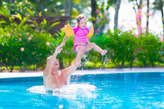 父亲和使用在游泳池的女婴 库存图片