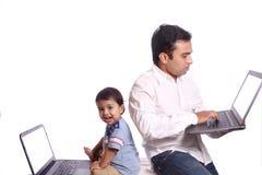 父亲和使用他们的膝上型计算机的愉快的儿子 免版税库存照片