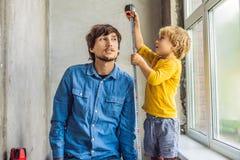 父亲和儿子一起修理窗口 修理房子  免版税库存图片