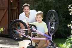 父亲和儿子一起清洁自行车 图库摄影