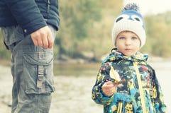 父亲和儿子做并且使由秋天叶子做的一条小船下水,童年, instagram的作用 免版税库存照片