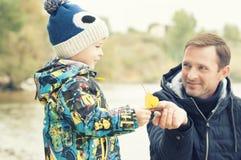 父亲和儿子做并且使由秋天叶子做的一条小船下水,童年, instagram的作用 免版税图库摄影
