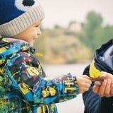 父亲和儿子做并且使由秋天叶子做的一条小船下水,童年, instagram的作用 库存照片