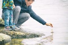 父亲和儿子做并且使由秋天叶子做的一条小船下水,童年, instagram的作用 库存图片