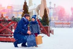 父亲和儿子冬天购物的在城市,节日,购买礼物 图库摄影