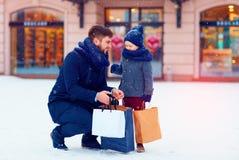 父亲和儿子冬天购物的在城市,节日,购买礼物 库存照片