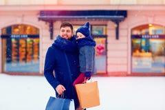 父亲和儿子冬天购物的在城市,节日,购买礼物 免版税图库摄影