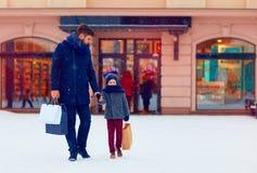 父亲和儿子冬天购物的在城市,节日 免版税图库摄影