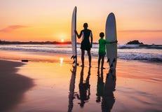 父亲和儿子冲浪者在日落海滩停留 图库摄影