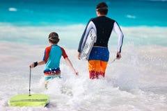 父亲和儿子冲浪 库存照片