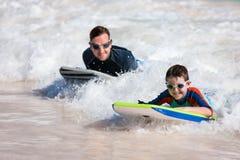 父亲和儿子冲浪 免版税图库摄影