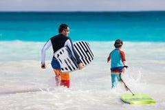 父亲和儿子冲浪 免版税库存图片