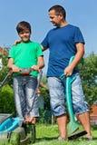 父亲和儿子准备好一些草坪割 库存照片