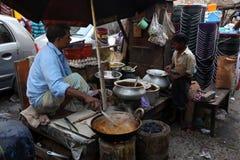 父亲和儿子准备简单的街道食物室外在加尔各答 免版税库存照片