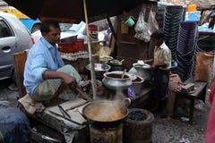 父亲和儿子准备简单的街道食物 免版税库存照片