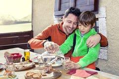 父亲和儿子吃午餐在瑞士山中的牧人小屋 库存照片