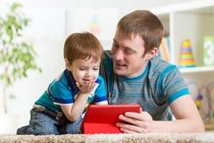 父亲和儿子哄骗与片剂计算机的戏剧 免版税库存图片