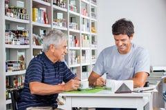父亲和儿子喝咖啡在表上 图库摄影