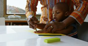 父亲和儿子在一张纸的图画剪影在桌在家4k上 股票录像
