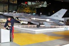 父亲和儿子在一架J-215战斗机附近在全国军事博物馆在Soesterberg,荷兰 库存照片