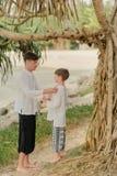 父亲和儿子在一棵树下在印地安裤子 库存图片