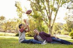 父亲和儿子在公园放松,投掷橄榄球 库存图片