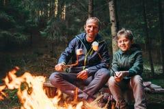 父亲和儿子在前面烤在营火的蛋白软糖糖果 库存图片