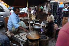 父亲和儿子在加尔各答准备简单的街道食物 库存图片