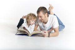 父亲和儿子在地板读一本书 免版税库存图片
