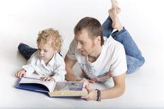 父亲和儿子在地板读一本书 免版税图库摄影