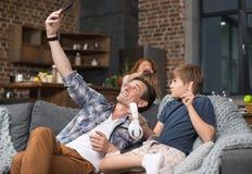 父亲和儿子在客厅拍在细胞巧妙的电话的Selfie照片坐长沙发 免版税库存图片
