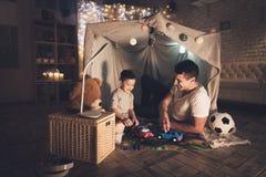 父亲和儿子在家使用与在地毯路的玩具汽车在晚上 库存图片