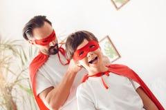 父亲和儿子在家站立人的superheroe服装的栓结在微笑男孩的面具快乐 库存照片