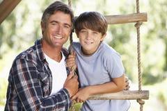 父亲和儿子在树上小屋的庭院里 图库摄影