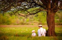 父亲和儿子在树下坐春天草坪 免版税库存图片