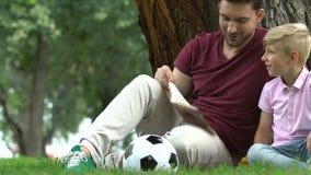 父亲和儿子在活跃足球比赛,家庭通信以后的阅读书 股票录像