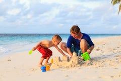 父亲和儿子在海滩的大厦沙堡 免版税库存图片