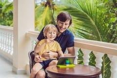 父亲和儿子在热带谈话与朋友和家庭在录影电话使用片剂和无线耳机 免版税库存图片