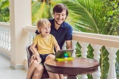 父亲和儿子在热带谈话与朋友和家庭在录影电话使用片剂和无线耳机 库存图片