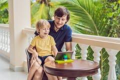 父亲和儿子在热带谈话与朋友和家庭在录影电话使用片剂和无线耳机 图库摄影