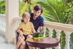 父亲和儿子在热带谈话与朋友和家庭在录影电话使用片剂和无线耳机 库存照片