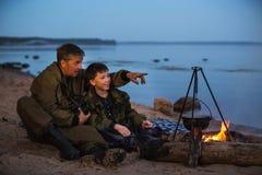 父亲和儿子在篝火附近 免版税库存照片