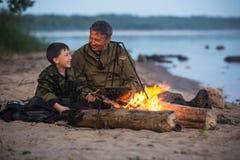 父亲和儿子在篝火附近 库存照片