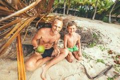 父亲和儿子在自制小屋和戏剧坐在Robinzones 免版税库存照片
